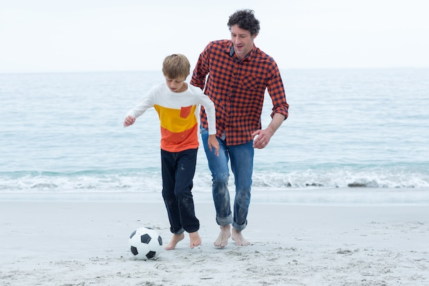 Отец и сын играют в футбол на пляже Premium Фотографии