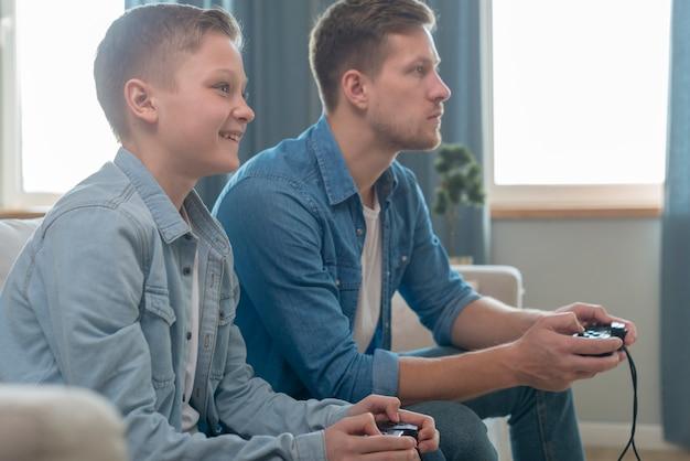 Отец и сын вместе играют в видеоигры Бесплатные Фотографии
