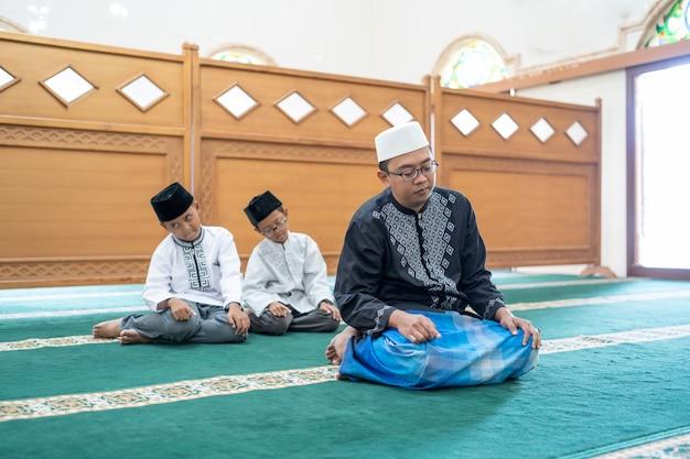 Отец и сын вместе молятся в мечети Premium Фотографии