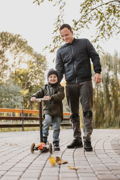 Отец и сын на детском самокате Premium Фотографии