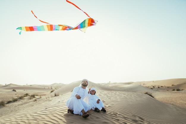 Отец и сын проводят время в пустыне Premium Фотографии