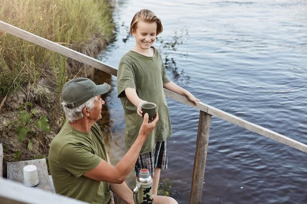 Отец и сын, проводить время вместе на берегу реки или озера, старший человек, давая чашку чая из термоса своему внуку, семья позирует на деревянные лестницы, ведущей к воде, отдых на красивой природе. Premium Фотографии