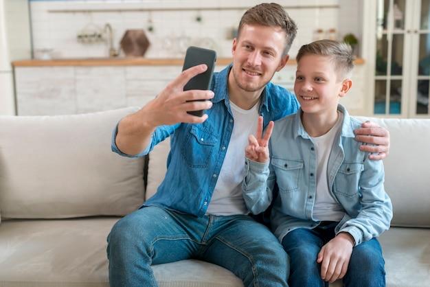 Отец и сын фотографируют Premium Фотографии