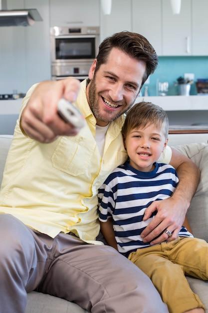 Отец и сын смотрят телевизор вместе на диване Premium Фотографии