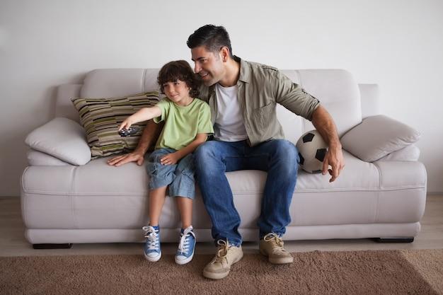 Отец и сын с футболом смотрят телевизор в гостиной Premium Фотографии