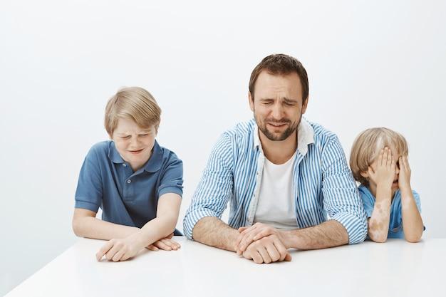Отец и сыновья расстроены, пока мама на работе. портрет голодной недовольной европейской семьи мальчиков и папы, сидящей за столом и плачущей Бесплатные Фотографии