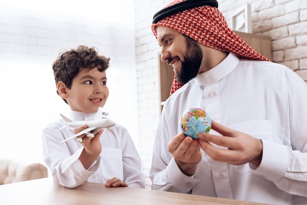 Father arab tells son about flight of aircraft. Premium Photo