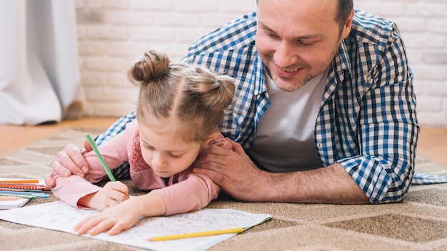 Father assisting girl in drawing while lying on carpet at home Free Photo