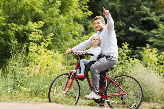 Father on bicycle pointing for daughter Free Photo