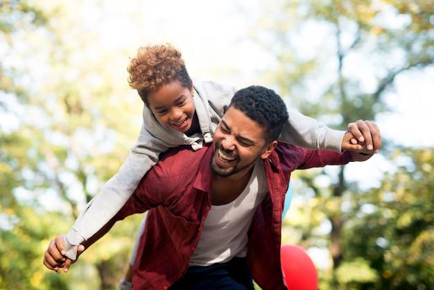 Отец несет дочь на спине с раскинутыми руками Бесплатные Фотографии