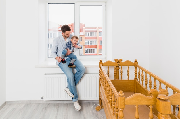 Father carrying his baby boy son sitting on window sill looking at wooden empty crib Free Photo