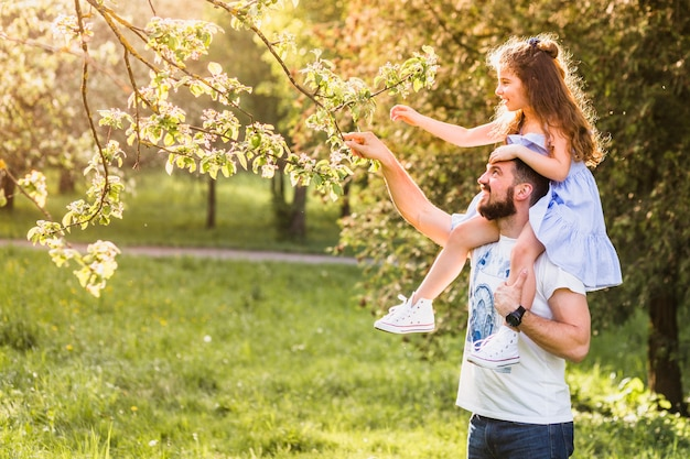 Father carrying his daughter on shoulder for touching tree branch Free Photo