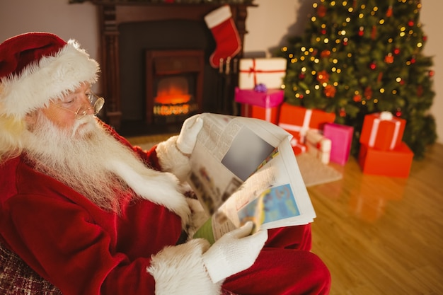 Father christmas reading newspaper on the couch Premium Photo