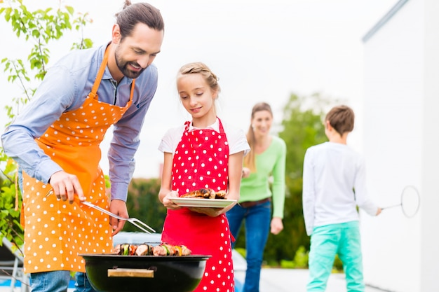 Father and daughter barbecue together Premium Photo