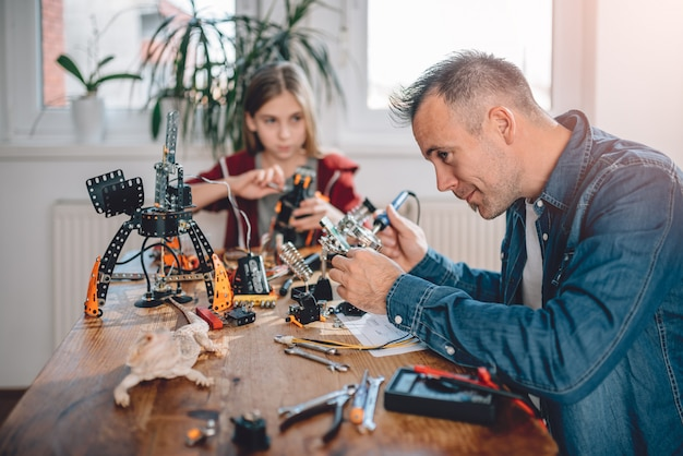 Father and daughter building robot Premium Photo