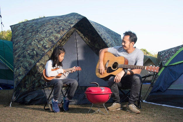 Father and daughter at camping playing ukulele and guitar Premium Photo