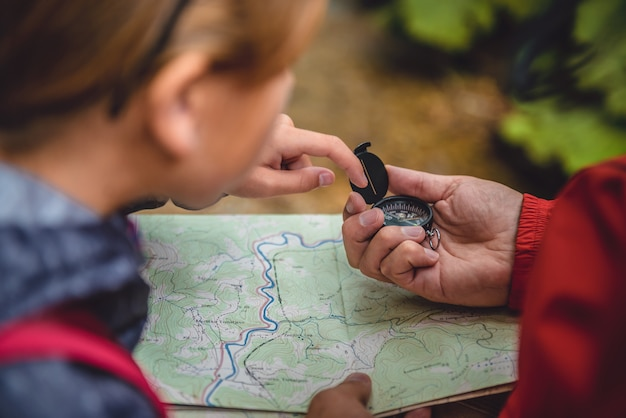 Father and daughter hiking in forest and checking map Premium Photo