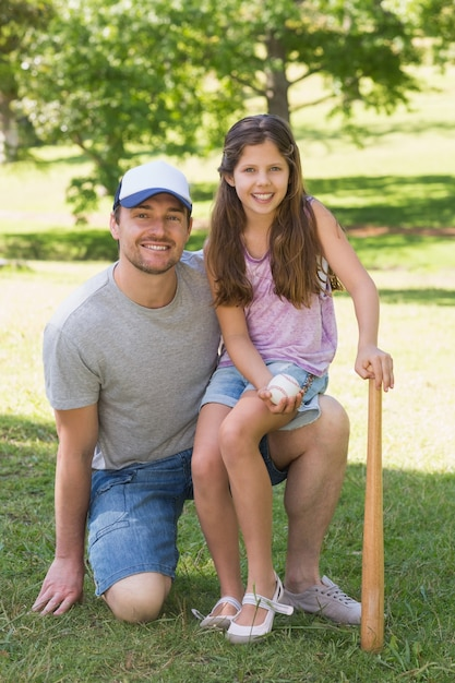 Father and daughter holding baseball bat in park Premium Photo