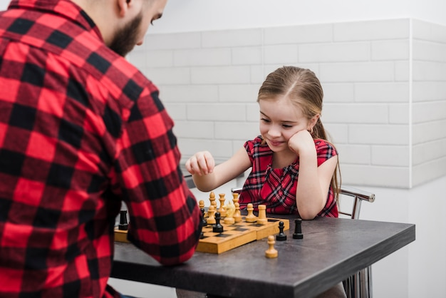 Father and daughter playing chess on fathers day Free Photo