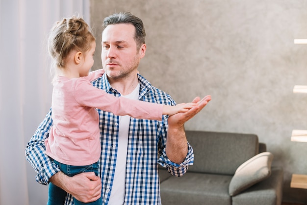 Father and daughter playing clapping game while looking at each other Free Photo