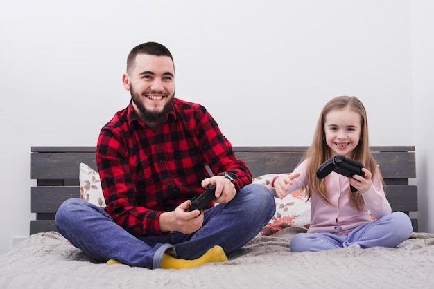 Father and daughter playing console Free Photo