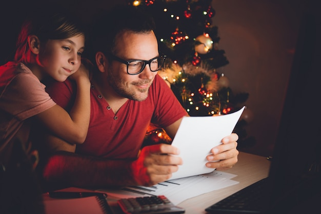 Father and daughter reading christmas wish list Premium Photo