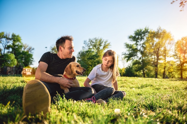 Father and daughter relaxing at park with dog Premium Photo