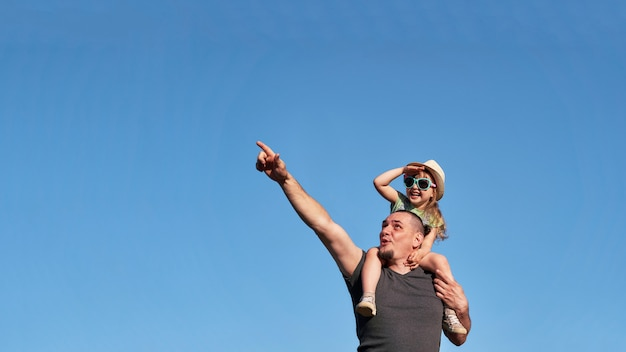 Father and daughter on shoulders happily rejoice. Premium Photo