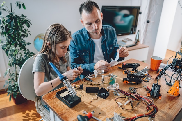 Father and daughter working on electronics components Premium Photo