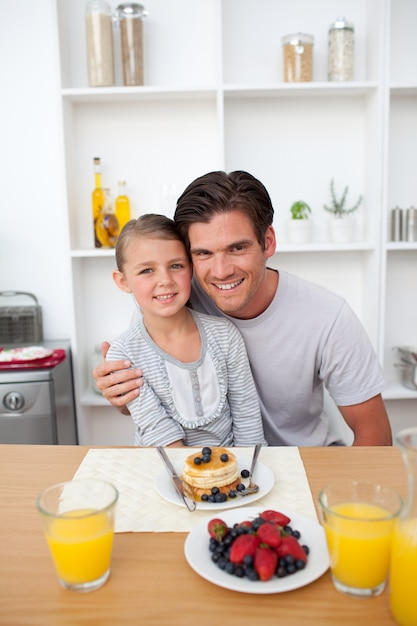 Father eating pancakes with his daughter in the kitchen Premium Photo