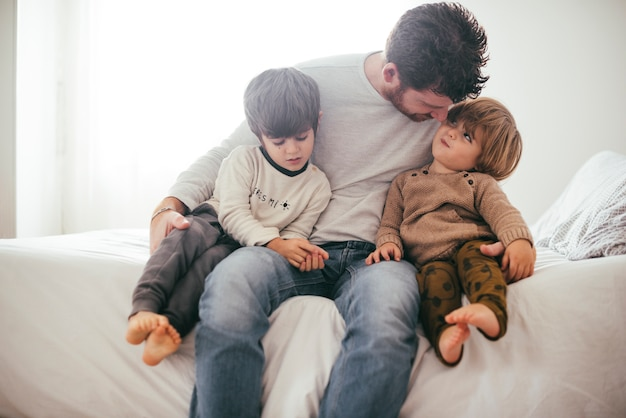 Father embracing toddler sons Premium Photo