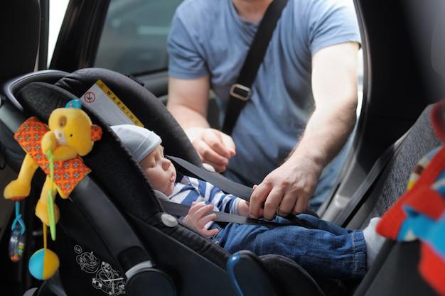 Father fasten his little son in car seat Premium Photo