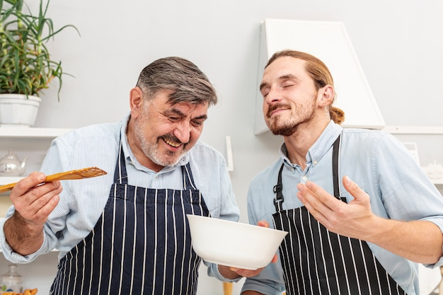 Father and funny son tasting a dish Free Photo