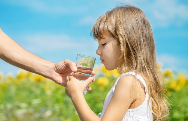 The father gives the child water in the background of the field Premium Photo