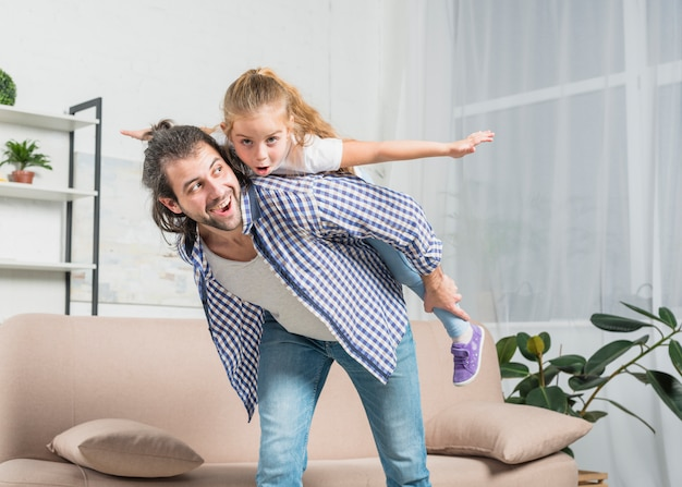 Father giving a piggy back ride to his daughter Free Photo