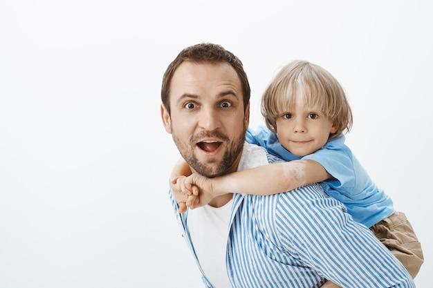 Отец скачет на спине милого белокурого сына с витилиго. портрет беззаботных красивых папы и малыша, обнимающихся Бесплатные Фотографии