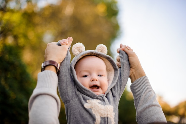 Father hands raising a cute smiling little son in the park Premium Photo