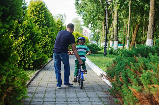Father help son to ride bicycle in summer park. back view Premium Photo