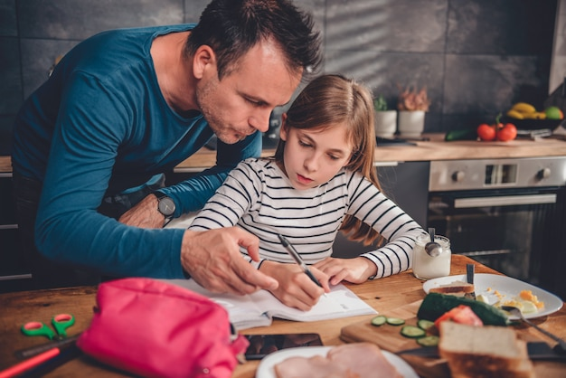 Father helping daughter with homework in kitchen Premium Photo