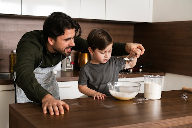 Father helping son to make dough Free Photo