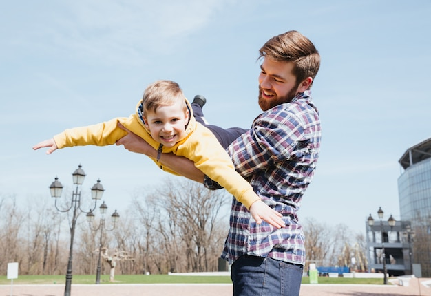 Father and his little son playing together in a park Free Photo