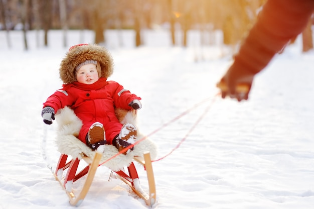 Father and his toddler son having fun in winter park. games with fresh snow Premium Photo