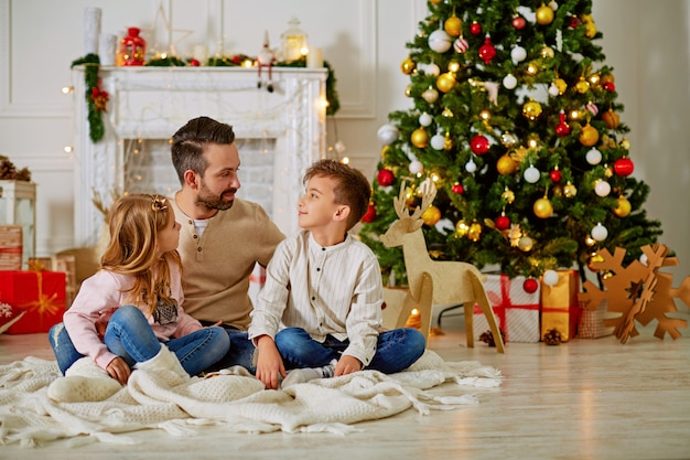 Father and his two little children sitting by fireplace chimney on christmas eve time Premium Photo