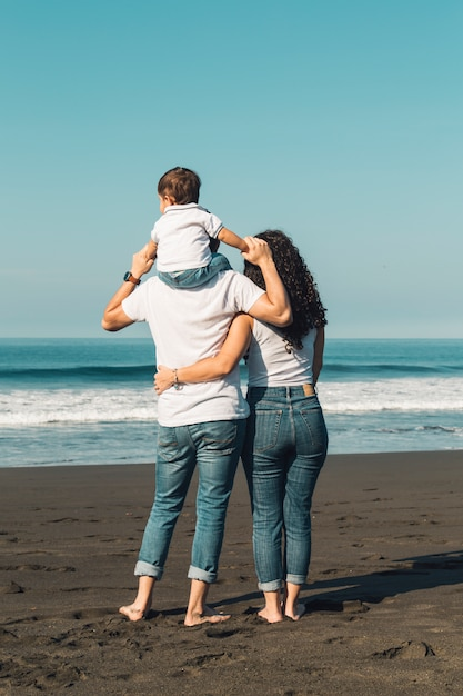 Father holding baby on neck and hugging with wife on beach Premium Photo