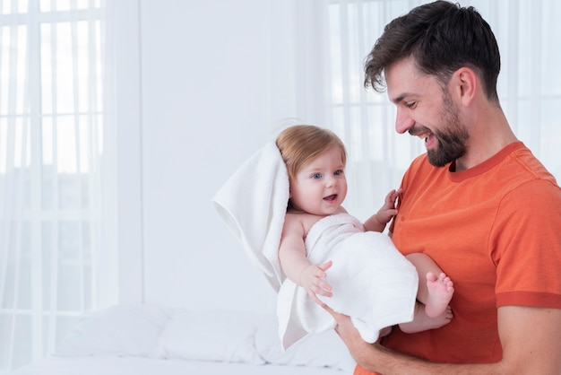 Father holding baby in towel Free Photo