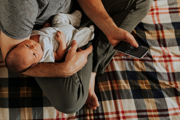 Father holding his baby while using his phone Premium Photo