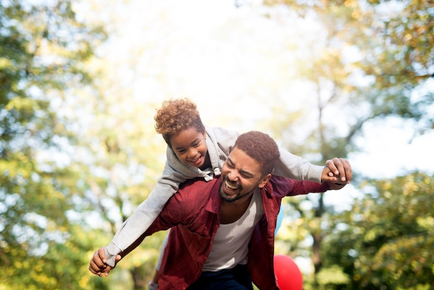 Father holding his daughter on shoulders and laughing Free Photo