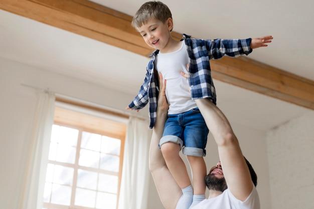 Отец держит своего сына в воздухе в помещении Бесплатные Фотографии