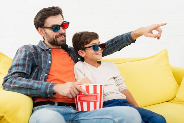 Father holding popcorn and watching a movie with his son Free Photo