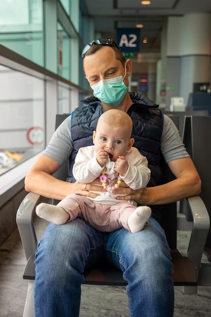 医療用マスクの父と空港で飛行機の搭乗を待っている彼の娘 Premium写真
